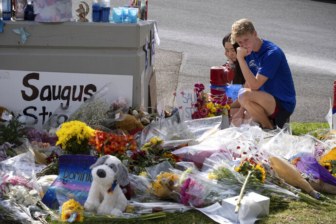 Saugus high students Katie Thanaet and Tyler Wilson look over items left at a memorial in front of the school Tuesday, Nov. 19, 2019. Students were allowed back on campus to collect their belongings left behind after the tragic shooting last Thursday. Classes will resume at the high school on Dec. 2. (David Crane/The Orange County Register via AP)