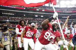 Oklahoma defensive lineman Neville Gallimore (90) plants a University of Oklahoma flag after the Sooners 30-23 overtime win over Baylor in an NCAA college football game for the Big 12 Conference championship, Saturday, Dec. 7, 2019, in Arlington, Texas. (Ian Maule/Tulsa World via AP)