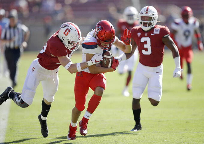 Arizona's Tayvian Cunningham, center, is tackled by Stanford's Stuart Head, left, and Malik Antoine, right, during the first half of an NCAA college football game Saturday, Oct. 26, 2019, in Stanford, Calif. (AP Photo/Ben Margot)