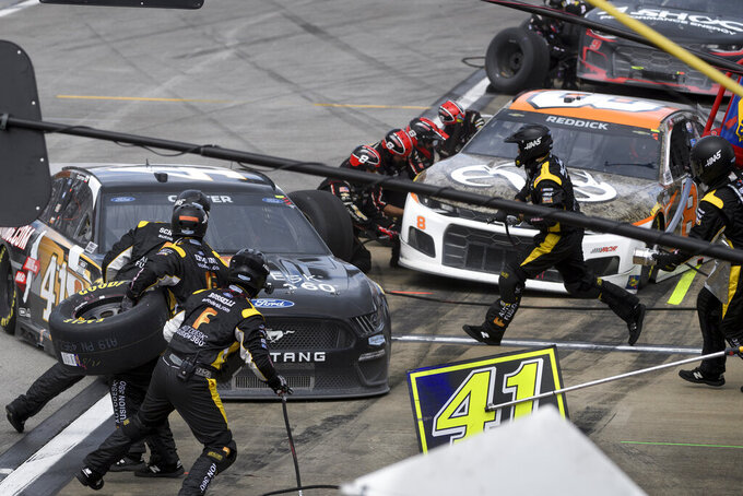 Cole Custer, left, and Tyler Reddick, right, make pit stops during a NASCAR Cup series auto race Monday, Oct. 4, 2021, in Talladega, Ala. (AP Photo/John Amis)