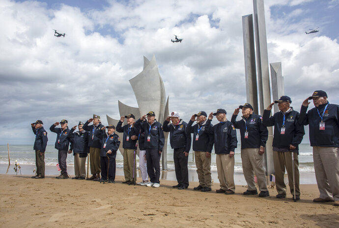 FILE - In this June, 3, 2019, file photo, World War II veterans from the United States salute as they pose in front of Les Braves monument at Omaha Beach in Saint-Laurent-sur-Mer, Normandy, France. Ceremonies marking the 75th anniversary of D-Day reminded us that an entire generation is fading from the world stage. (AP Photo/Rafael Yaghobzadeh, File)