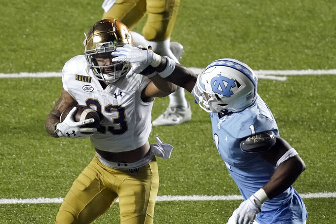 Notre Dame running back Kyren Williams (23) runs while North Carolina defensive back Kyler McMichael (1) tries to tackle him during the second half of an NCAA college football game in Chapel Hill, N.C., Friday, Nov. 27, 2020. (AP Photo/Gerry Broome)