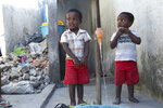 Children wait to fill up a bucket with water from a tap in a neighbourhood in Beira, Mozambique, Tuesday, April, 2, 2019. Mozambican and international health workers raced Monday to contain a cholera outbreak in the cyclone-hit city of Beira and surrounding areas, where the number of cases has jumped to more than 1,000. (AP Photo/Tsvangirayi Mukwazhi)