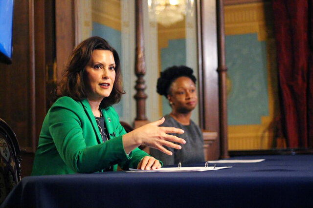 In a pool photo provided by the Michigan Office of the Governor, Michigan Gov. Gretchen Whitmer addresses the state during a speech in Lansing, Mich., Thursday, April 9, 2020. The governor signed an executive order extending her prior