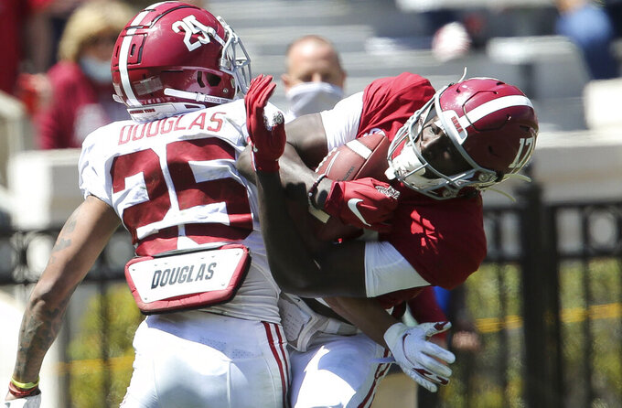 FILE - In this April 17, 2021, file photo, Alabama wide receiver Agiye Hall (17) makes a catch as defensive back DJ Douglas (25) defends during Alabama's spring NCAA college football game at Bryant-Denny Stadium in Tuscaloosa, Ala. Alabama is hoping that search for receiver help to complement John Metchie III pays immediate dividends. The top-ranked Crimson Tide, which could be called Wide Receiver U. lately, brought in four highly rated recruits.  (Gary Cosby/The Tuscaloosa News via AP, File)