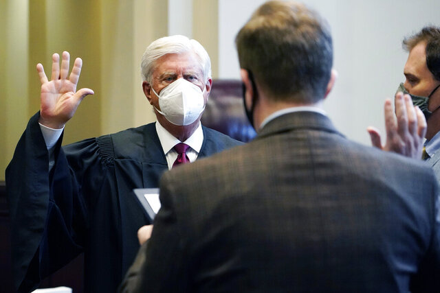Mississippi Supreme Court Chief Justice Mike Randolph, left, recites his oath of office as administered by Clerk of Courts Jeremy Whitmire, center, Monday, Jan. 4, 2021, in the En Banc Courtroom at the Gartin Justice Building in Jackson, Miss. Randolph, the longest serving member of the court with over 16 years of service, and two other justices were sworn into office Monday morning, to start their new eight-year terms. (AP Photo/Rogelio V. Solis)