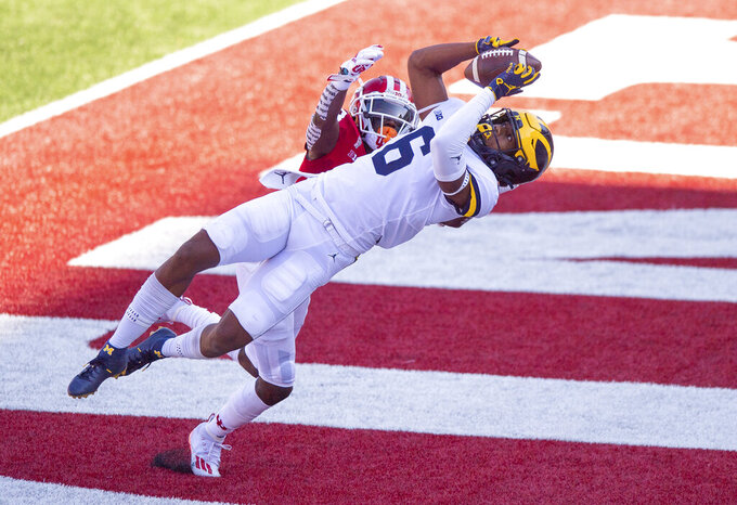 Michigan wide receiver Cornelius Johnson (6) catches a pass in the end zone for a touchdown as Indiana defensive back Jaylin Williams (23) defends during the first half of an NCAA college football game Saturday, Nov. 7, 2020, in Bloomington, Ind. (AP Photo/Doug McSchooler)