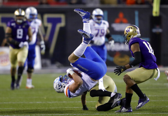 Boise State tight end John Bates (85) is upended, after a pass reception, by Washington defensive back Trent McDuffie, center, during the first half of the Las Vegas Bowl NCAA college football game Saturday, Dec. 21, 2019, in Las Vegas. Washington defensive back Cameron Williams is at right. (AP Photo/Steve Marcus)