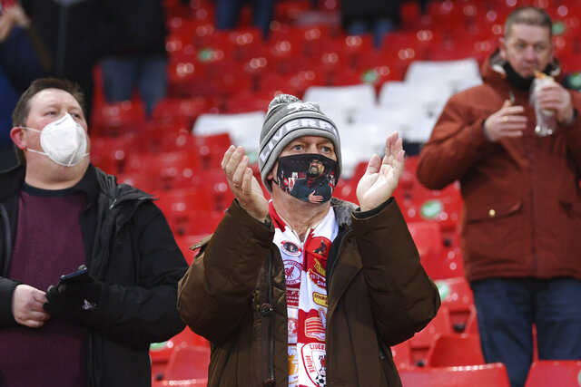 A Liverpool fans with a Jurgen Klopp protective face mask applauds before the start of an English Premier League soccer match between Liverpool and West Bromwich Albion at the Anfield stadium in Liverpool, England, Sunday Dec. 27, 2020. (Stu Forster/Pool via AP)