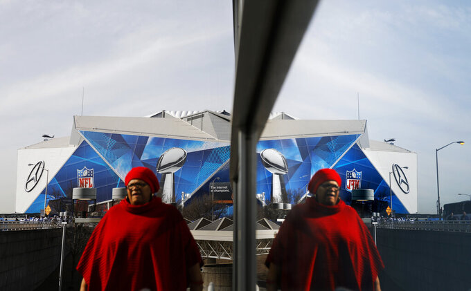 Mercedes-Benz Stadium is reflected in a window ahead of Sunday's NFL Super Bowl 53 football game between the Los Angeles Rams and New England Patriots in Atlanta, Friday, Feb. 1, 2019. (AP Photo/David Goldman)