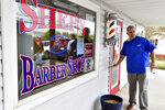 Brad Shepler, a barber who resumed cutting hair despite it being prohibited under Pennsylvania Gov. Tom Wolf's coronavirus shutdown orders, walks out of his barber shop to hold a new conference with local state lawmakers, Thursday, May 14, 2020 in Enola, Pa. Shepler also received a warning letter from the state's licensing agency. (AP Photo/Marc Levy)