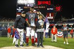 Washington Nationals' Howie Kendrick holds his MVP trophy as he celebrates with his family after Game 4 of the baseball National League Championship Series against the St. Louis Cardinals Tuesday, Oct. 15, 2019, in Washington. The Nationals won 7-4 to win the series 4-0. (AP Photo/Patrick Semansky)