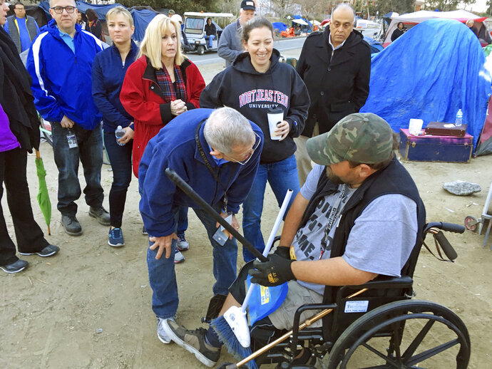 U.S. District Judge David Carter speaks with 36-year-old Shane Allen, who is homeless and in a wheelchair, during a tour of a homeless encampment along the Santa Ana River in Anaheim, Calif., Wednesday, Feb. 14, 2018. Minutes later, county officials said they had arranged for Allen to move to a motel room. Carter demanded that Orange County officials provide answers about what federal funding is available to feed and temporarily house people if they are moved. (AP Photo/Amy Taxin)
