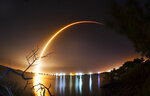 This photo shows a time exposure from the shore of the Banana River near Port Canaveral of the launch of the SpaceX Falcon 9 rocket from Cape Canaveral, Fla., Thursday, Feb. 21, 2019  An Israeli spacecraft blasted off to the moon in an attempt to make the country's first lunar landing, following a launch Thursday night by SpaceX. (Malcolm Denemark/Florida Today via AP)