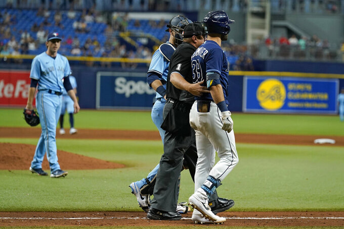 Tampa Bay Rays' Kevin Kiermaier, right, is held back by home plate umpire Bruce Dreckman and Toronto Blue Jays catcher Danny Jansen after Kiermaier was hit with a pitch by starting pitcher Ryan Borucki, right, during the eighth inning of a baseball game Wednesday, Sept. 22, 2021, in St. Petersburg, Fla. (AP Photo/Chris O'Meara)