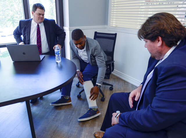 FILE - Jeffery Ryans points at his ankle as he discusses his encounter with Salt Lake City police at his attorney's office on Aug. 5, 2020, in Salt Lake City. Salt Lake City's police dog apprehension program will remain suspended indefinitely, the police chief announced, after an officer ordered a dog to attack Ryans, who had put his hands in the air. Weeks after body camera footage of an officer directing a dog to attack Ryans came to light, the department ordered an internal affairs audit of its K9 apprehension program, Chief Mike Brown told reporters Friday, Sept. 25, 2020. (Leah Hogsten/The Salt Lake Tribune via AP, File)