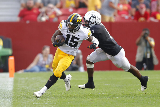 Iowa running back Tyler Goodson (15) runs the ball as Iowa State defensive back Isheem Young (1) pushes him out of bounds during the second half of an NCAA college football game, Saturday, Sept. 11, 2021, in Ames, Iowa. Iowa won 27-17. (AP Photo/Matthew Putney)