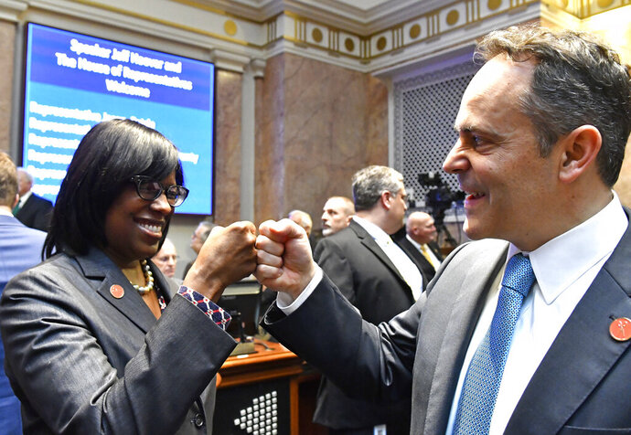 FILE - In this Jan. 3, 2017 file photo, Kentucky Gov. Matt Bevin, right, and Kentucky Lt. Governor Jenean Hampton bump fists as they await the swearing in of Jeff Hoover as Speaker of the Kentucky House of Representatives in Frankfort, Ky.  Hampton pushed back Friday, Oct. 4, 2019 against Bevin's explanation for dropping her from his reelection ticket, saying she was unaware of any disagreements about her priorities until the governor discussed their political split at a tea party meeting. (AP Photo/Timothy D. Easley)