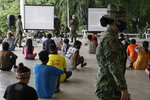 Residents that were rounded up for violating quarantine protocols listen to a lecture given by police in Quezon city, Philippines on Wednesday, Aug. 12, 2020. The residents were recorded and given lectures on community quarantine protocols before they were released as the capital and outlying provinces undergo another lockdown due to rising COVID-19 cases. (AP Photo/Aaron Favila)
