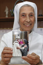 FILE -- In this Aug. 27, 2019 file photo, ST. Mary's School Vice Principal Sister Ana Rosa Sivori shows a picture taken with Pope Francis, at the girls' school in Udon Thani, about 570 kilometers (355 miles) northeast of Bangkok, Thailand. Sister Ana Rosa Sivori, originally from Buenos Aires in Argentina, shares a great-grandfather with Jorge Mario Bergoglio, who, six years ago, became Pope Francis. So, she and the pontiff are second cousins. In his visit to Thailand Pope Francis will be reunited with his second cousin, who has lived in Thailand since 1966 and will serve as Francis' official translator there. (AP Photo/Sakchai Lalit)