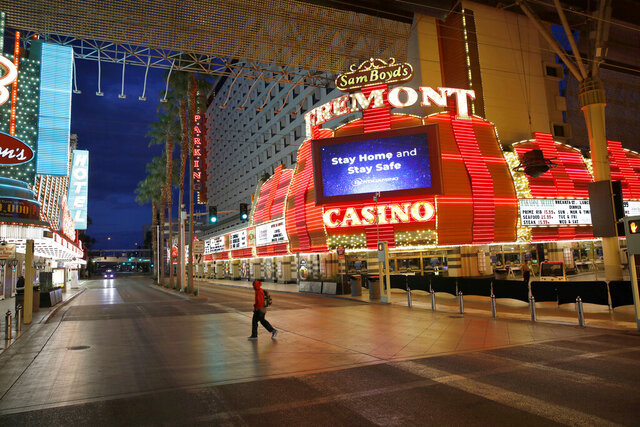 FILE - In this March 21, 2020, file photo, a man walks along a usually busy Fremont Street after casinos were ordered to shut down due to the coronavirus outbreak in Las Vegas. The coronavirus pandemic has been particularly brutal to the tourism-dependent economies of Nevada and Hawaii, lifting the unemployment rate in both states to about one-quarter of the workforce. (AP Photo/John Locher, File)