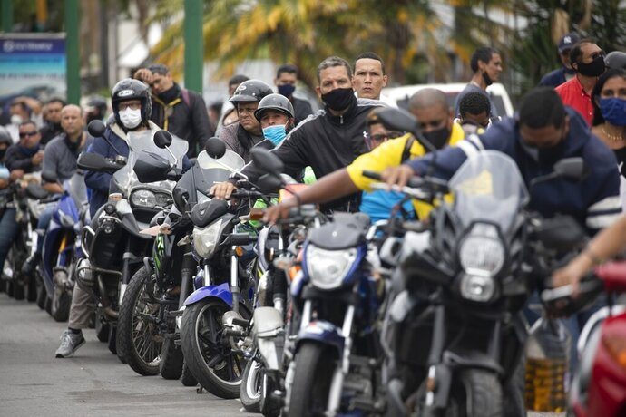 Motorcyclists wearing masks amid the new coronavirus pandemic wait their turn to fill up at a gas station in Caracas, Venezuela, Tuesday, Sept 8, 2020. Gasoline shortages have returned to Venezuela, sparking mile-long lines in the capital as international concerns mounted that Iran yet again may be trying to come to the South American nation's rescue. (AP Photo/Ariana Cubillos)