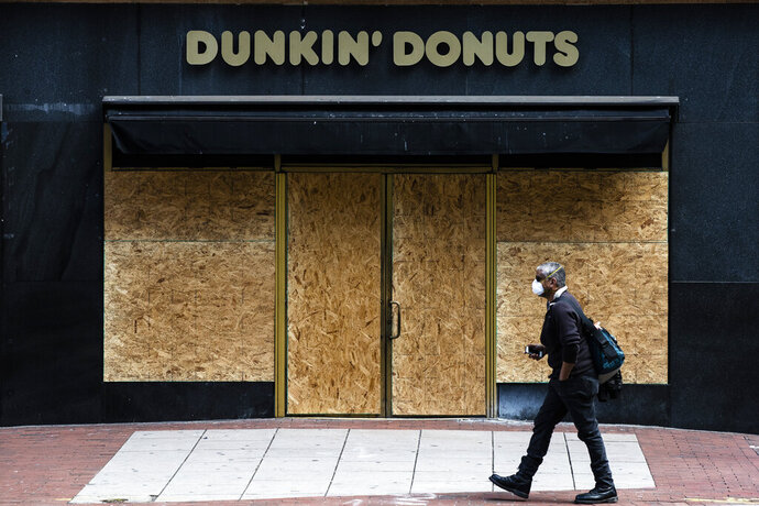 A person wearing protective masks due to coronavirus fears walks past a boarded up business in Philadelphia, Tuesday, March 24, 2020. (AP Photo/Matt Rourke)