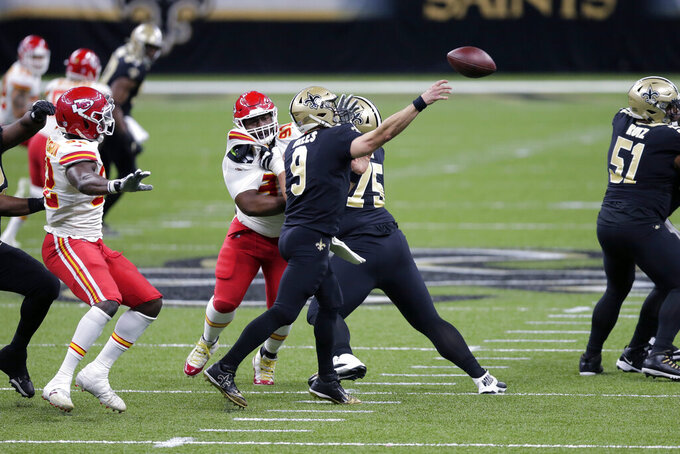 New Orleans Saints quarterback Drew Brees (9) passes under pressure from Kansas City Chiefs defensive tackle Derrick Nnadi (91) and defensive end Tanoh Kpassagnon in the first half of an NFL football game in New Orleans, Sunday, Dec. 20, 2020. (AP Photo/Brett Duke)