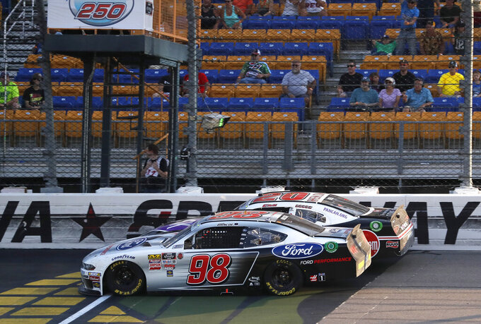Chase Briscoe (98) passes Christopher Bell(20) with seven laps to go in a NASCAR Xfinity Series auto race, Saturday, July 27, 2019, at Iowa Speedway in Newton, Iowa. Briscoe won the race. (AP Photo/Matthew Putney)
