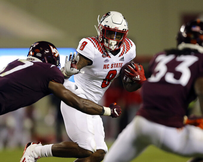 North Carolina State running back Ricky Person Jr. (8) runs the ball while chased by Virginia Tech defender Divine Deablo, left, and Keonta Jenkins (33) during the second quarter of an NCAA college football game Saturday, Sept. 26, 2020, in Blacksburg, Va. (Matt Gentry/The Roanoke Times via AP, Pool)