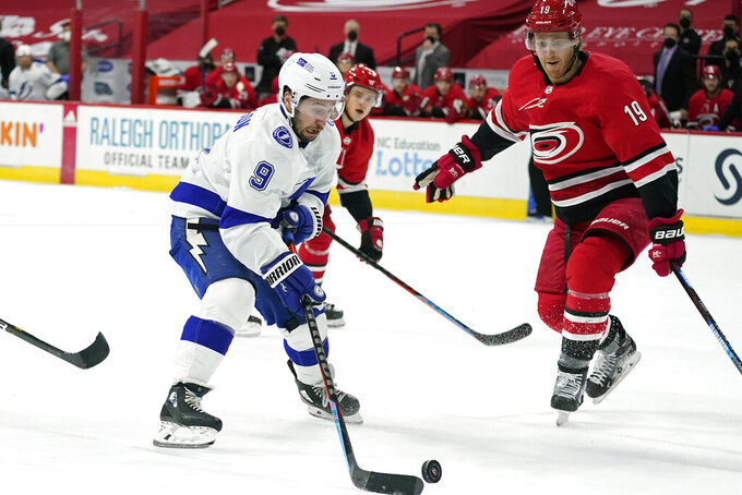 Tampa Bay Lightning center Tyler Johnson (9) looks to shoot as Carolina Hurricanes defenseman Dougie Hamilton (19) defends during the first period of an NHL hockey game in Raleigh, N.C., Monday, Feb. 22, 2021. (AP Photo/Gerry Broome)