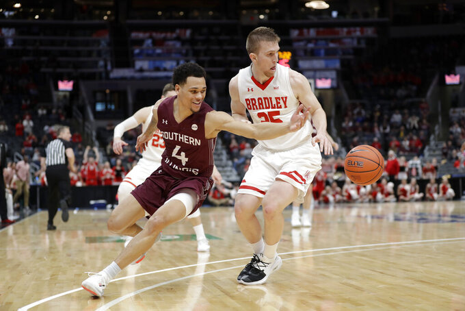 Southern Illinois' Eric McGill (4) and Bradley's Nate Kennell reach for a loose ball during the second half of an NCAA college basketball game in the quarterfinal round of the Missouri Valley Conference men's tournament Friday, March 6, 2020, in St. Louis. (AP Photo/Jeff Roberson)
