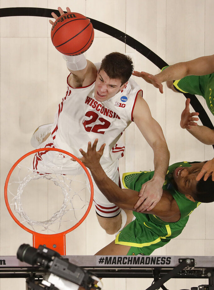 Wisconsin forward Ethan Happ (22) shoots against Oregon forward Francis Okoro, bottom right, during the first half of a first-round game in the NCAA men's college basketball tournament Friday, March 22, 2019, in San Jose, Calif. (AP Photo/Ben Margot)