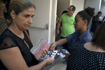 In this Sept. 2, 2018, photo, a woman distributes leaflets that features evangelical pastor Silas Malafaia with two political candidates, to congregants filing out of the Assembly of God Victory in Christ Church in Rio de Janeiro, Brazil. While the Vatican frowns on clergy running for office, many evangelical leaders plunge into politics. (AP Photo/Leo Correa)