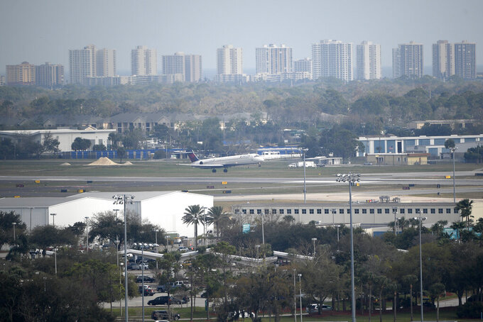 A Delta Airlines passenger jet lands at Daytona International Airport with oceanfront condominiums in the background during a NASCAR Xfinity Series auto race at Daytona International Speedway Saturday, Feb. 16, 2019, in Daytona Beach, Fla. (AP Photo/Phelan M. Ebenhack)