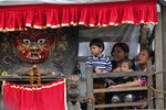 Devotees sit next to a statue of god Bhairabh during Indra Jatra festival, an eight-day festival that honors Indra, the Hindu god of rain, in Kathmandu, Nepal, Friday, Sept. 13, 2019. The girl child revered as the Living Goddess Kumari is pulled around Kathmandu in a wooden chariot, families gather for feasts and at shrines to light incense for the dead, and men and boys in colorful masks and gowns representing Hindu deities dance to the beat of traditional music and devotees' drums, drawing tens of thousands of spectators to the city's old streets.  (AP Photo/Niranjan Shrestha)