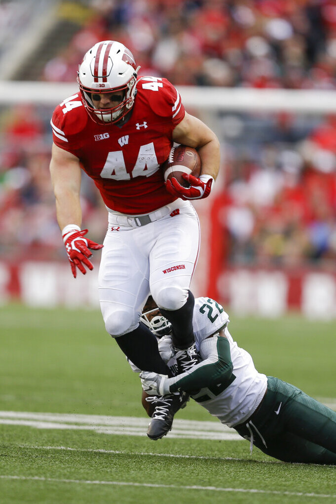 Wisconsin fullback John Chenal, left, gets tripped up by Michigan State cornerback Josiah Scott, right, during the first half of an NCAA college football game Saturday, Oct. 12, 2019, in Madison, Wis. (AP Photo/Andy Manis)