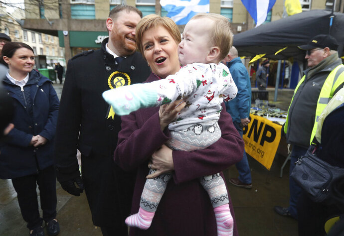 SNP leader Nicola Sturgeon holds a baby in Dalkeith, whilst on the General Election campaign trail in Midlothian, Scotland, Wednesday Dec. 4, 2019. Britain goes to the polls on Dec. 12. The independence of Scotland from the rest of the United Kingdom is not on the ballot, but it's uppermost on the minds of many voters here as they make their final choices ahead of the national election next week. (Andrew Milligan/PA via AP)