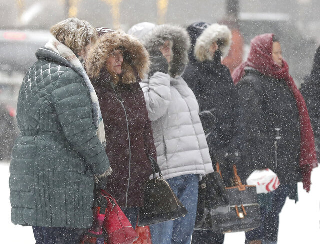 Commuters wait for a bus at the corner of 6th St. and 2nd Ave. as a powdery dusting of snow falls ahead of a large expected snowstorm Friday, Jan. 17, 2020, in downtown Minneapolis, Minn. (David Joles/Star Tribune via AP)