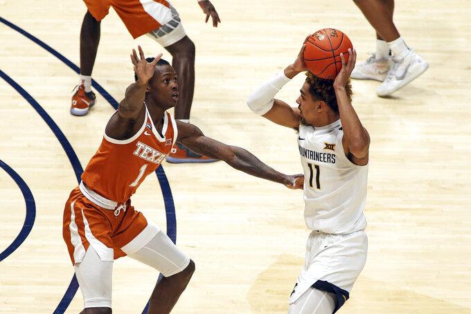 West Virginia forward Emmitt Matthews Jr. (11) passes while defended by Texas guard Andrew Jones (1) during the half of an NCAA college basketball game Saturday, Jan. 9, 2021, in Morgantown, W.Va. (AP Photo/Kathleen Batten)