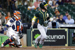 Oakland Athletics designated hitter Jed Lowrie, right, watches his hit for a single in front of Houston Astros catcher Martin Maldonado, left, during the third inning of a baseball game Thursday, July 8, 2021, in Houston. (AP Photo/Michael Wyke)