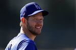 Los Angeles Dodgers pitcher Clayton Kershaw looks on during spring training baseball camp Friday, Feb. 14, 2020, in Phoenix. (AP Photo/Gregory Bull)