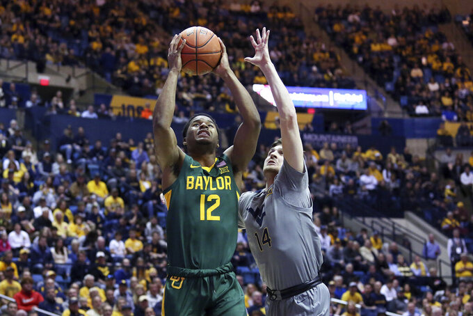 Baylor guard Jared Butler (12) shoots ahead of West Virginia guard Chase Harler (14) during the first half of an NCAA college basketball game Saturday, March 7, 2020, in Morgantown, W.Va. (AP Photo/Kathleen Batten)