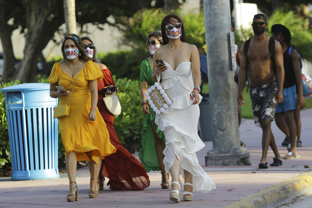 People wearing protective face masks walk along Ocean Drive during the coronavirus pandemic, Friday, July 24, 2020, in Miami Beach, Fla. Masks are mandated both indoors and outdoors in Miami Beach. People found not wearing a mask are subject to a civil fine of $50. (AP Photo/Lynne Sladky)
