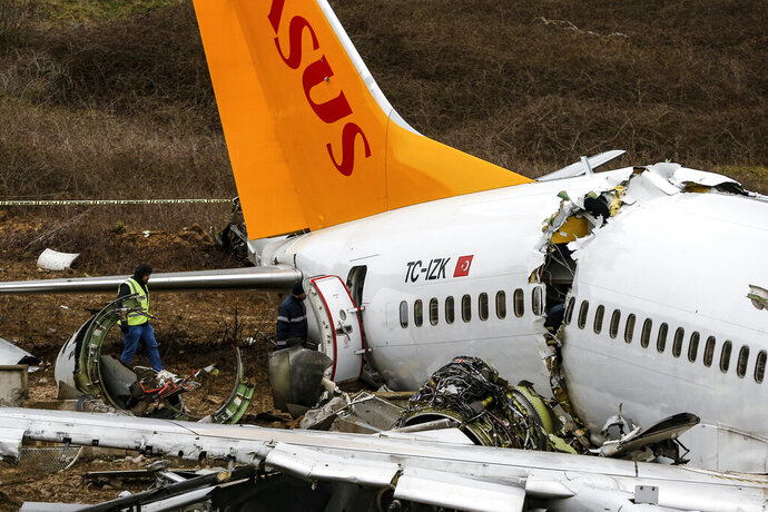Officials work on the wreckage of a plane operated by Pegasus Airlines after it skidded Wednesday off the runway at Istanbul's Sabiha Gokcen Airport, in Istanbul, Thursday, Feb. 6, 2020. Flights resumed Thursday after the airliner skidded off a runway, killing three people and injuring dozens. The Boeing 737 landed during strong winds and heavy rain and overshot the runway. It skidded about 50-60 meters (yards) before it dropped into the ditch from a height of about 30 meters (98 feet) (AP Photo/Emrah Gurel)