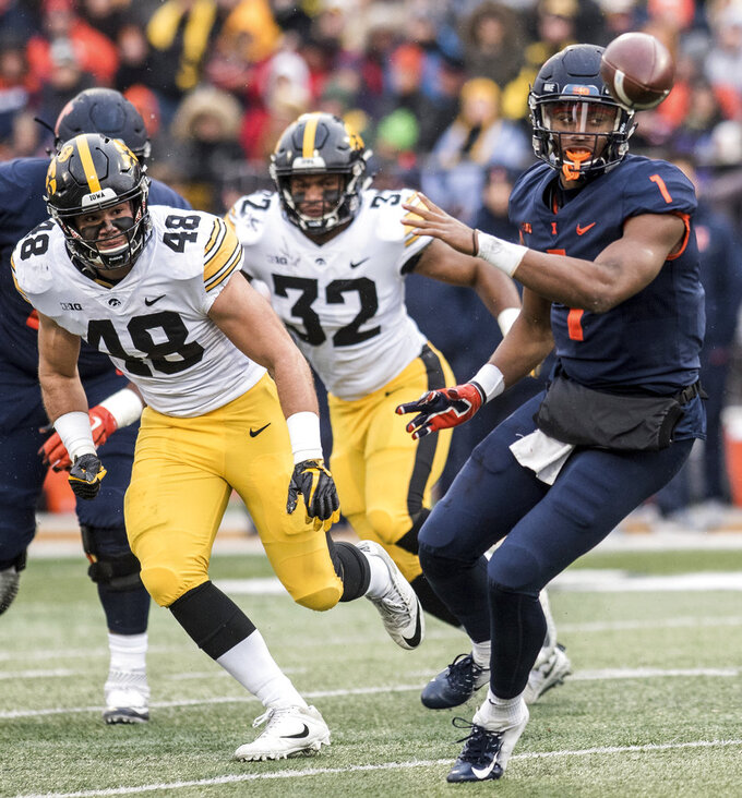 Illinois quarterback A.J. Bush, Jr. (1) throws a shuffle pass as Iowa's Jack Hockaday (48) and Djimon Colbert (32) defend in the first half of a NCAA college football game, Saturday, Nov. 17, 2018, in Champaign, Ill. (AP Photo/Holly Hart)