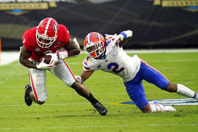 Georgia running back Zamir White, left, is stopped by Florida defensive back Brad Stewart Jr. (2) during the first half of an NCAA college football game, Saturday, Nov. 7, 2020, in Jacksonville, Fla. (AP Photo/John Raoux)