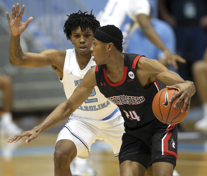 North Carolina's Caleb Love (2) defends against Northeastern's Shaquille Walters (24) during the first half of an NCAA college basketball game Wednesday, Feb. 17, 2021, in Chapel Hill, N.C. (Robert Willett/The News & Observer via AP)