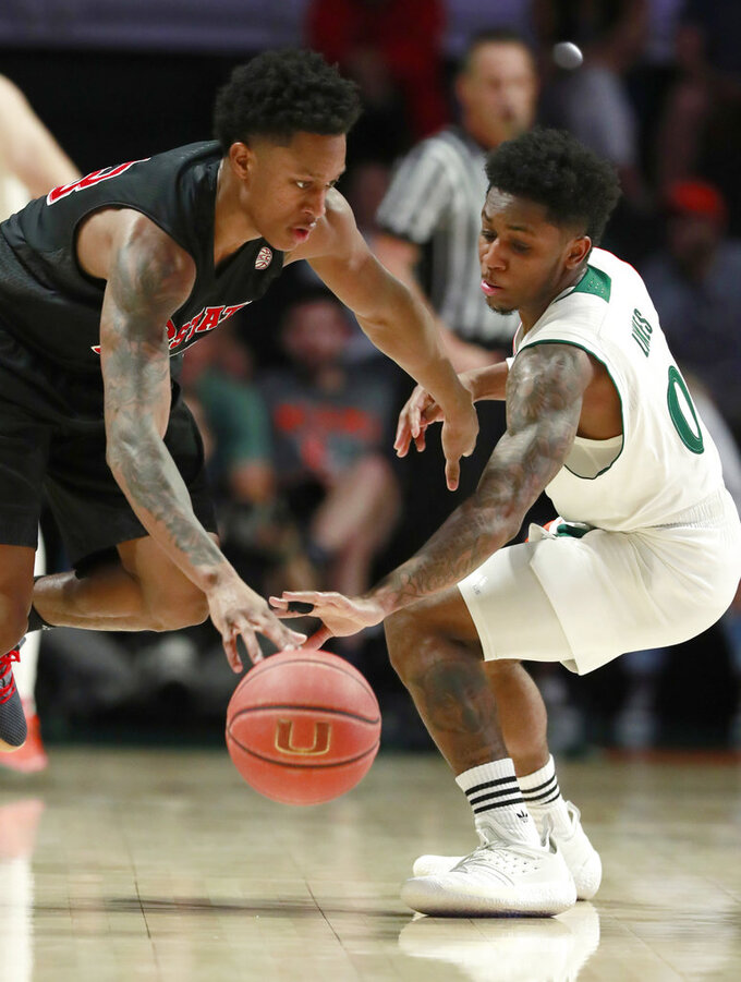 North Carolina State guard C.J. Bryce, left, attempts to drive past Miami guard Chris Lykes (0) during the first half of an NCAA college basketball game, Thursday, Jan. 3, 2019, in Coral Gables, Fla. (AP Photo/Wilfredo Lee)