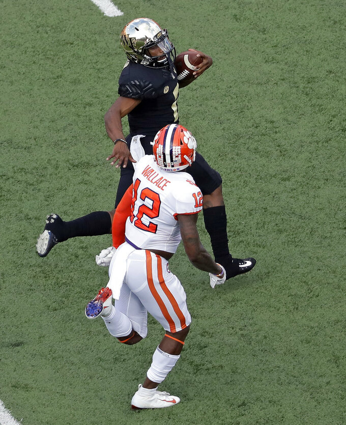 Wake Forest's Kendall Hinton, top, runs for a long gain as Clemson's Christian Wilkins, bottom, pursues during the second half of an NCAA college football game in Charlotte, N.C., Saturday, Oct. 6, 2018. (AP Photo/Chuck Burton)